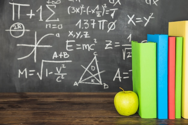 Books and apple on table near blackboard