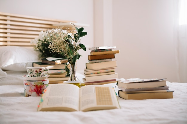 Books and bouquet on bed in morning
