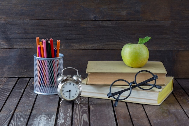 Books, colored pencils, alarm clock, green apple