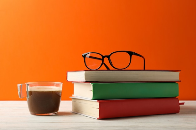 Books, cup of coffee and glasses on wooden table, space for text