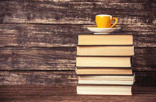 Books and cup of coffee on wooden table