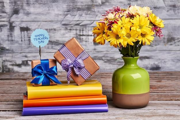 책, 꽃, 선물 상자. 나무 배경에 다채로운 책입니다. 첫 번째 선생님을 축하합니다.