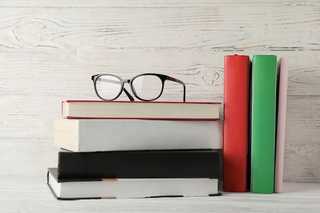 Books and glasses against wooden rustic background, space for text