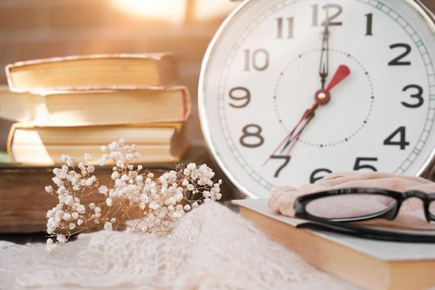 햇빛이 비치는 아침에 책 안경과 알람 시계
