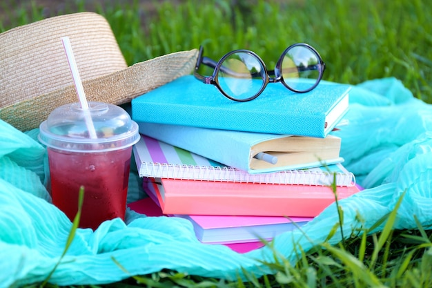 草のクローズアップで本、メガネ、飲み物