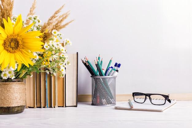 Книги, стаканы, фломастеры и букет цветов в вазе на белом