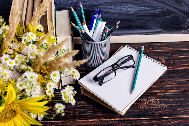 Books, glasses, markers and a bouquet of flowers in a vase on white