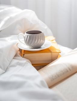 컵과 함께 침대에서 책