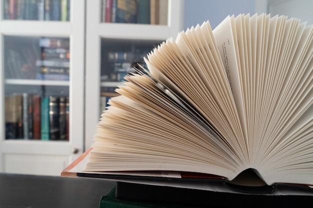 図書館の本、本棚を背景にした本のページを開く