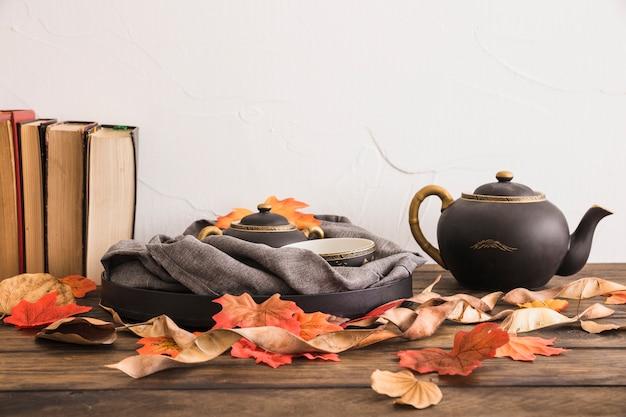 Books and leaves near tea set