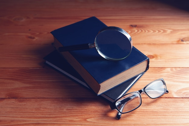 Books, magnifying glass and glasses on the table