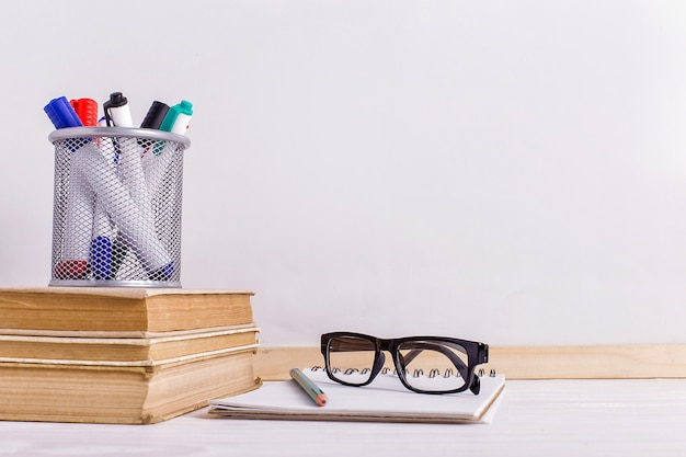 Books, markers, notebook, pencil and glasses on the table