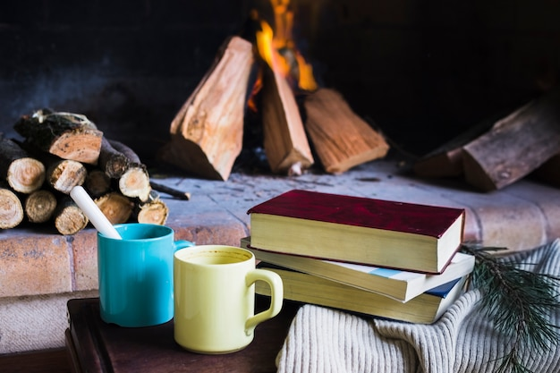Books and mugs near fireplace