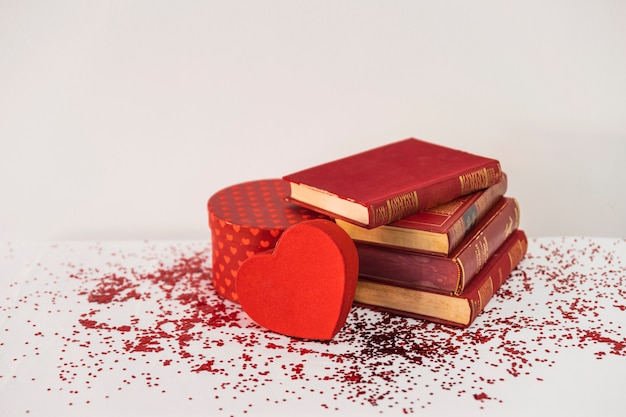 Books near present and ornament heart on table
