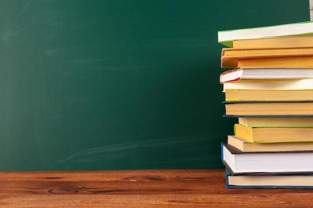 机の上の本、黒板背景