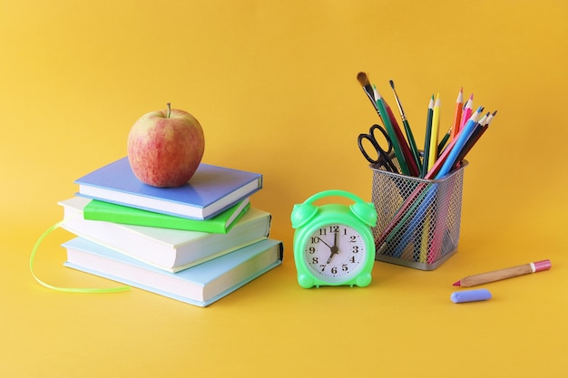 Books, pencils and alarm clock on bright background, home learning concept