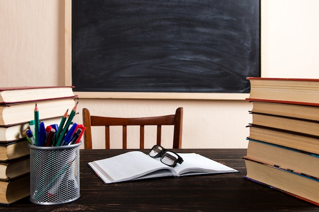 Книги, ручки, карандаши и очки на деревянном столе, против доске.