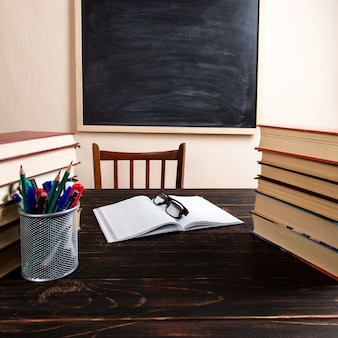 Books, pens, pencils and glasses on a wooden table, against a chalk board.