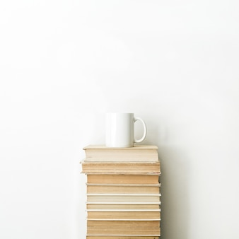 白い表面に本の山とコーヒーマグ