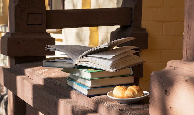 Books and a plate of croissants on the veranda. cozy place to read and relax
