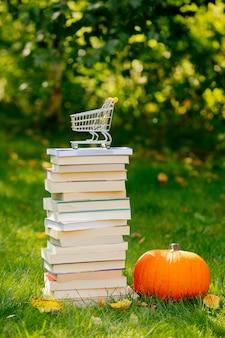 Books and pumpkin with shopping cart on green grass in a garden