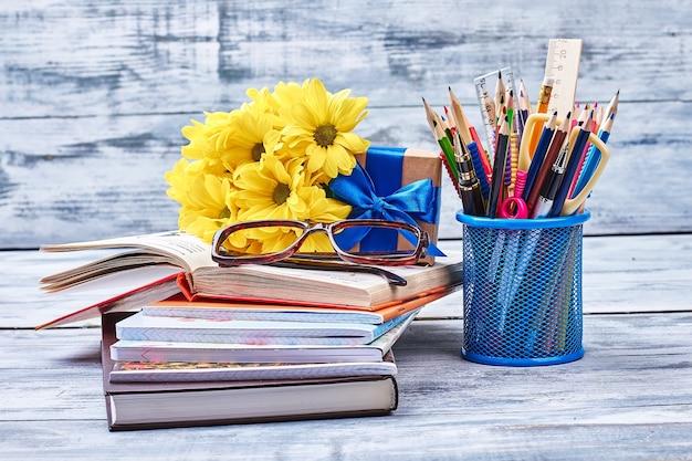 Книги, очки, цветы и канцелярские товары. цветы и подарочная коробка. знание - сила.