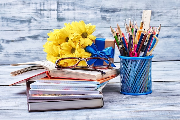 Books, spectacles, flowers and stationery. flowers and present box. knowledge is power.