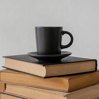 本は屋内に積み重ねられ、コーヒーカップ