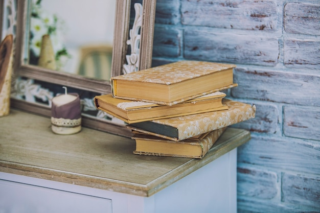 Books stack on the old table in the surface of mirrors, candles. tradition, training, education, reading, retro, vintage.