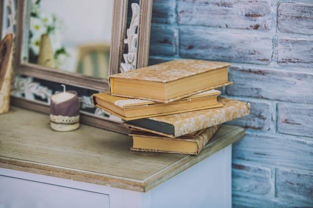 本は鏡やろうそくの表面の古いテーブルに積み上げられます。伝統、トレーニング、教育、読書、レトロ、ヴィンテージ。