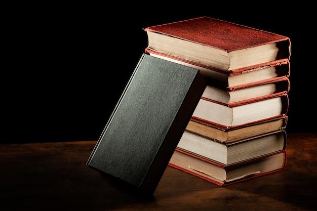 本は木製のテーブルに積み重ねられます