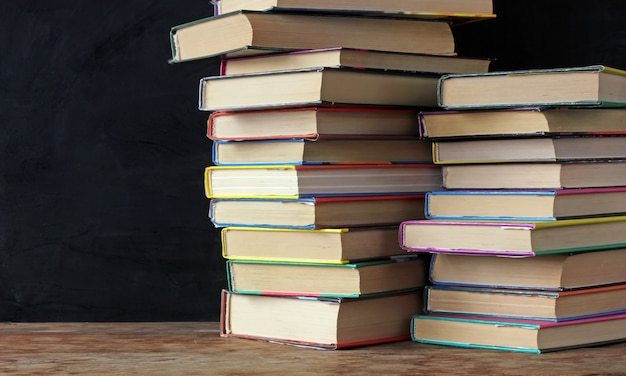 Books in stacks on the table of a school blackboard.