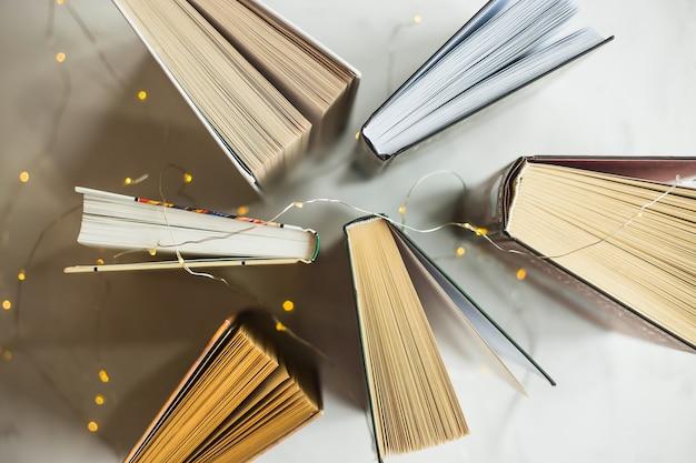 Книги стоят на столе с желтыми огнями гирлянды. концепция чтения