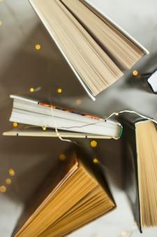 Книги стоят на столе с желтыми огнями гирлянды