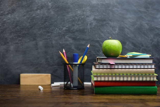 Books, stationery and education supplies on wooden desk in classroom