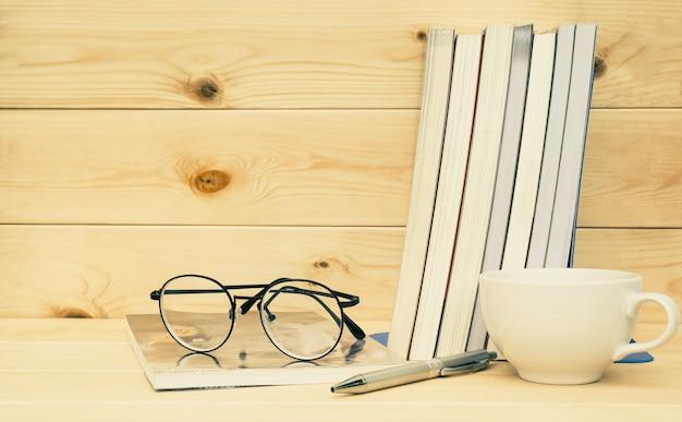 上記の眼鏡の本テーブルと木製の背景に眼鏡とコーヒーカップで予約