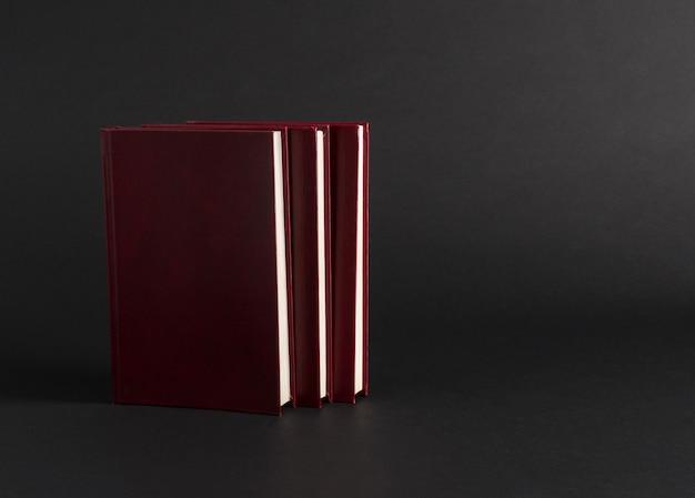 Книги с красной крышкой на черном фоне, изолированные. обратно в школу