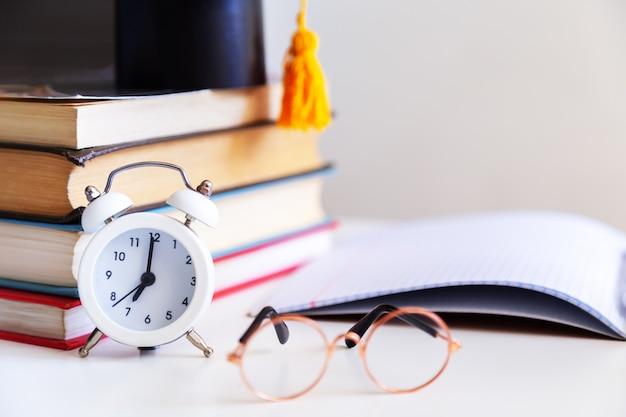 デスクトップ上の本、筆記剤、眼鏡、ノートブック、目覚まし時計。学校に戻る。学習と独学の概念。セレクティブフォーカス。