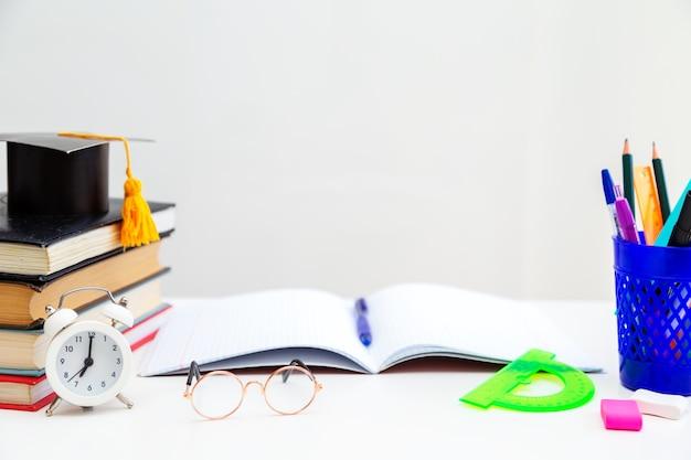デスクトップ上の本、筆記剤、眼鏡、ノートブック、目覚まし時計。学校に戻る。学習と独学の概念。