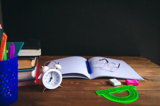 デスクトップ上の本、筆記剤、眼鏡、ノートブック、目覚まし時計。黒の背景。学習と独学の概念。セレクティブフォーカス。