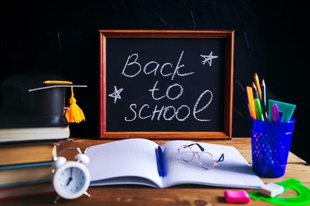 デスクトップ上の本、筆記剤、眼鏡、メモ帳、目覚まし時計。 「学校に戻る」というチョークのレタリング。学習と独学の概念。セレクティブフォーカス。