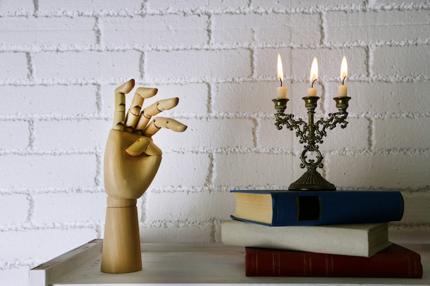 Bookshelf with books and candlestick on brick wall