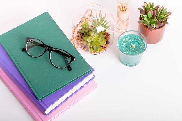 여러 가지 빛깔의 책, 집 식물 즙이 많은 책장, 그리고 텍스트를 위한 블랙 보드 프레임. 스승의 날, 세계 책의 날 배경. 다채로운 책, 칠판의 스택과 함께 정물