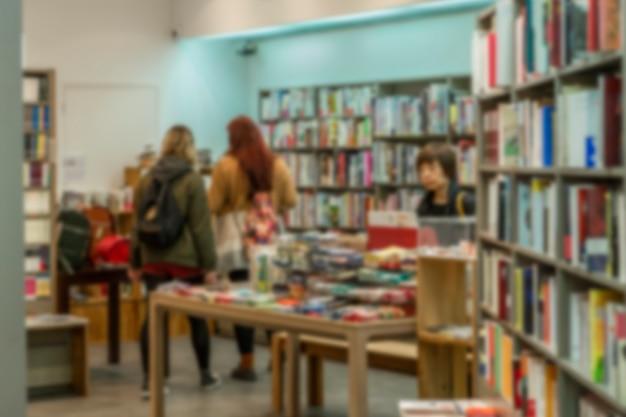 Интерьер книжного магазина с покупателями. образование и литература. размытый.