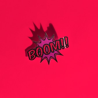 Boom comic text speech bubble pop art style sound effect on red backdrop