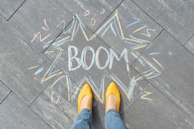 Boom written on gray sidewalk with women legs in yellow shoes
