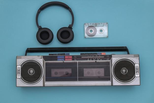 青の背景にラジカセオーディオテープレコーダー、ステレオヘッドフォン、オーディオカセット。レトロな80年代。上面図。フラットレイ