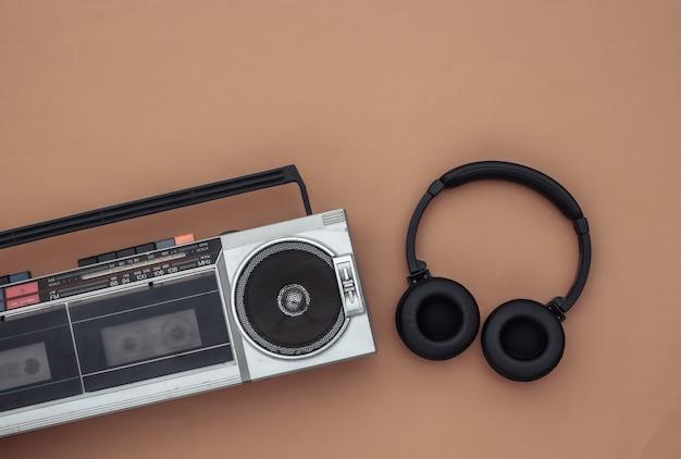ブームボックスオーディオテープレコーダー、茶色の背景にステレオヘッドフォン。レトロな80年代。上面図。フラットレイ
