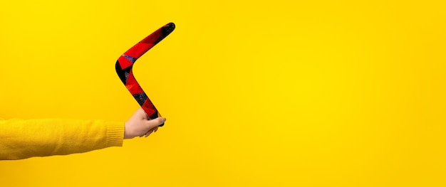 Boomerang in female hand over yellow background,