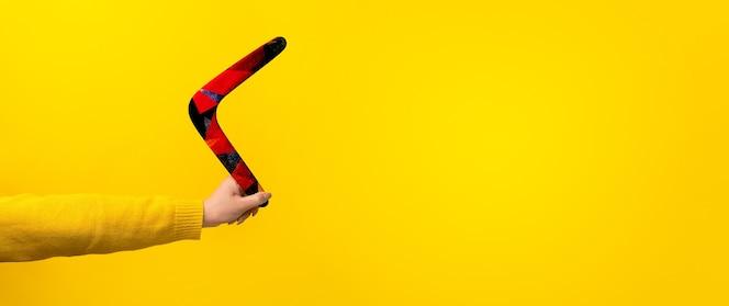 노란색 배경 위에 여성 손에 부메랑